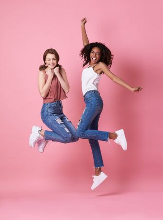 Portrait of two joyful young woman jumping and celebrating over pink background.