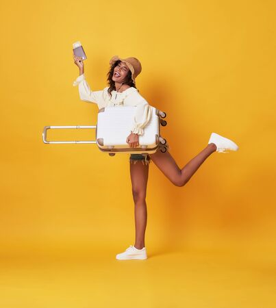 Cheerful young african woman dressed in summer clothes Holding a suitcase and passport and runing at copy space isolated over yellow background. Foto de archivo - 130127755