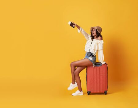 Cheerful young african woman dressed in summer clothes sitting on a suitcase and pointing finger at copy space isolated over yellow background. Banco de Imagens - 130127756