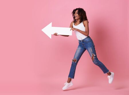 Portrait of shocked young african woman jumping with her arrow pointing at copy space isolated over pink banner background. Foto de archivo - 130127758