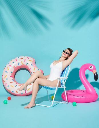 Cheerful attractive joyful delightful women dressed in nice swimwear sitting on a beach chair and rubber ring on bright blue background.