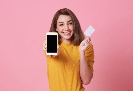 Portrait of a happy young woman showing at blank screen mobile phone and credit card isolated over pink background.