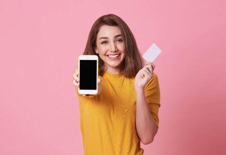 Ritratto di una giovane donna felice che mostra al telefono cellulare a schermo vuoto e alla carta di credito isolate su sfondo rosa.