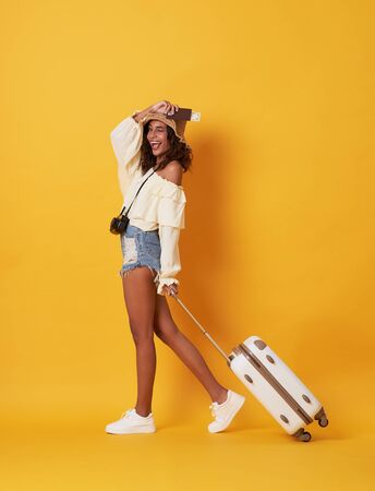 Cheerful young african woman dressed in summer clothes holding passport with money while standing with a suitcase isolated over yellow background. Banco de Imagens - 130127773