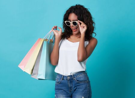 Portrait of an excited young african woman hand holding shopping bag and sunglasses isolated over blue background. 스톡 콘텐츠