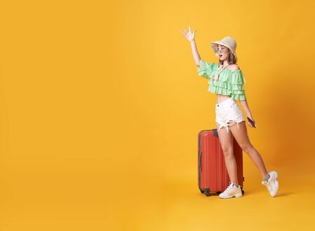 Cheerful young woman dressed in summer clothes standing with a suitcase and say hello at copy space isolated over yellow background.