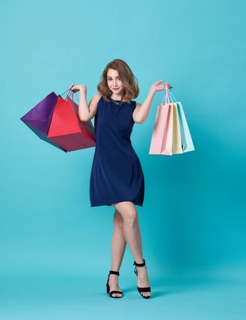 Happy beautiful young woman in blue dress and hand holding shopping bag isolated over blue background. 스톡 콘텐츠 - 130127794