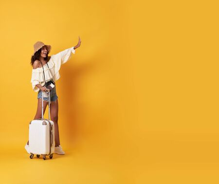 Cheerful young african woman dressed in summer clothes standing with a suitcase and say hello at copy space isolated over yellow background. Banco de Imagens