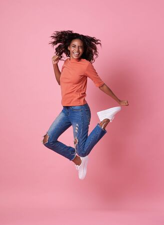 Portrait of a joyful young african woman in orange shirt jumping and celebrating over pink background.