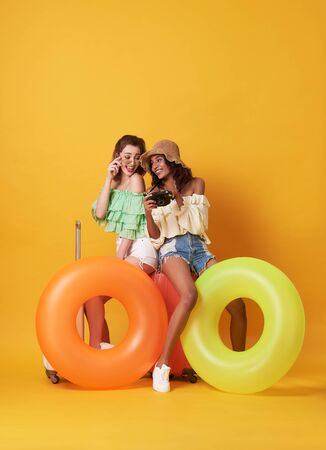 Cheerful friends woman dressed in summer clothes sitting on a suitcase and rubber ring isolated over yellow background. Banco de Imagens - 130127808