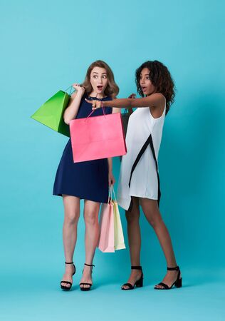 Portrait of two excited young woman hand holding shopping bag and with her finger pointing at copy space over blue background