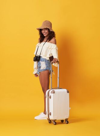 Cheerful young african woman dressed in summer clothes holding passport with money while standing with a suitcase isolated over yellow background. Banque d'images - 131956614