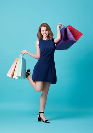 Happy beautiful young woman in blue dress and hand holding shopping bag isolated over blue background.