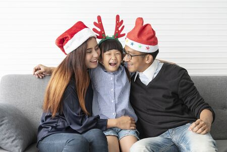 Family Asian mother and father with daughter celebration happy christmas together in livingroom at home. Banco de Imagens - 134082810