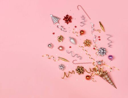 Christmas composition with decorations and ribbon with star confetti on pink pastel background. winter, new year concept. Flat lay, top view, copy space. Banco de Imagens - 134082352
