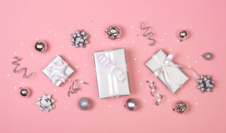 Christmas composition with decorations and gift box with star confetti on pink pastel background. winter, new year concept. Flat lay, top view, copy space. Banco de Imagens - 134082490