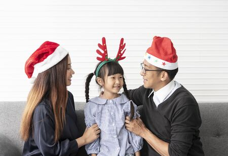 Family Asian mother and father with daughter celebration happy christmas together in livingroom at home. Banco de Imagens - 134082564