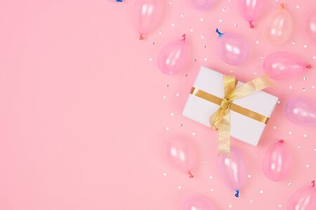 Gift box composition with decorations and balloon, confetti on pink pastel background. birthday, new year concept. Flat lay, top view, copy space. Banco de Imagens