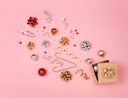 Christmas composition with decorations and gift box with star confetti on pink pastel background. winter, new year concept. Flat lay, top view, copy space. Banco de Imagens - 134082592