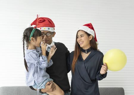 Family Asian mother and father with daughter celebration happy christmas together in livingroom at home. Banco de Imagens - 134082595