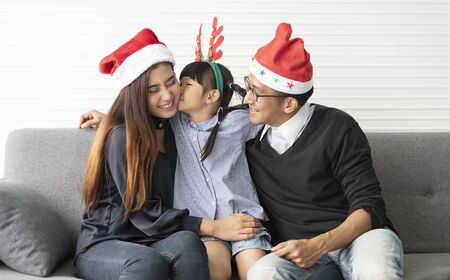 Family Asian mother and father with daughter celebration happy christmas together in livingroom at home. Banco de Imagens - 134082610
