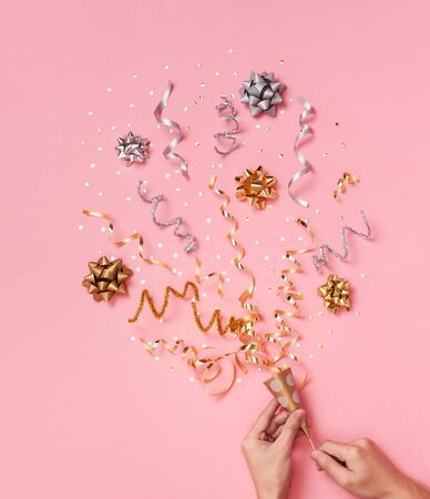 Christmas composition with decorations and ribbon with star confetti on pink pastel background. winter, new year concept. Flat lay, top view, copy space.