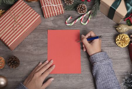Hand writing mock up greeting card for Merry Christmas and Happy new year with Christmas decoration on wood table. Banco de Imagens - 134082019