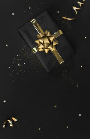 Gift box with decorations gold confetti on black background for christmas and new year concept. copy space
