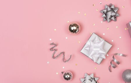 Christmas composition with decorations and gift box with star confetti on pink pastel background. winter, new year concept. Flat lay, top view, copy space. Banco de Imagens - 134082097