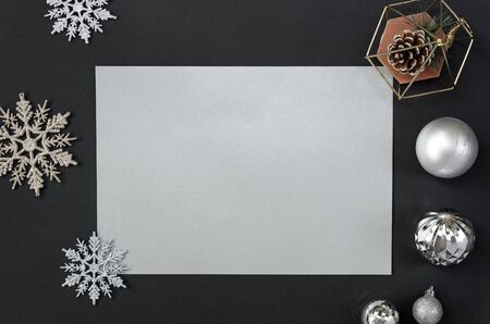 Mock up greeting paper card on black background with Christmas decorations and confetti. Invitation card design for text.