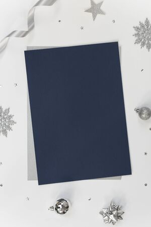 Mock up greeting paper card on white background with Christmas decorations and confetti. Invitation card design for text. Banco de Imagens