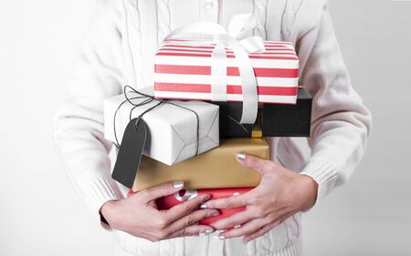 women hand holding gift box and paper tag isolated on white background for christmas and new year concept. Banco de Imagens