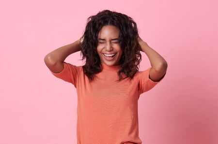 Excited beautiful african woman happiness wearing casual orange t-shirt isolated on pink background.
