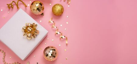 Christmas composition banner with decorations and gift box with star confetti on pink pastel background. winter, new year concept. Flat lay, top view, copy space.