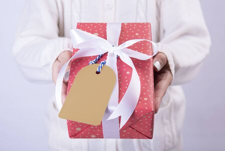 women hand holding red gift box and paper tag isolated on white background for christmas and new year concept.