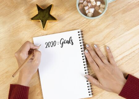 Hand writing mockup postcard for goals to do list on wooden background.Christmas and Happy new year resolution concept.