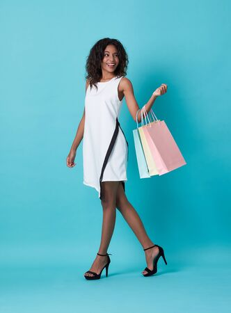 Happy beautiful young african woman in white dress and hand holding shopping bag isolated over blue background.