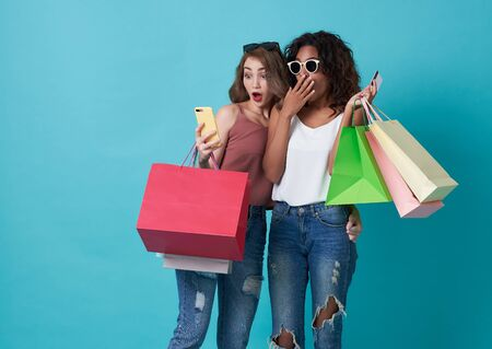 Portrait of two excited young woman hand holding mobile phone and shopping bag isolated over blue background. Banco de Imagens
