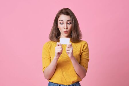 excited young woman in yellow shirt showing credit card isolated over pink background.