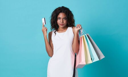 Young woman showing credit card and shopping bags isolated over blue background.