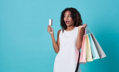 Excited young woman showing credit card and shopping bags isolated over blue background.