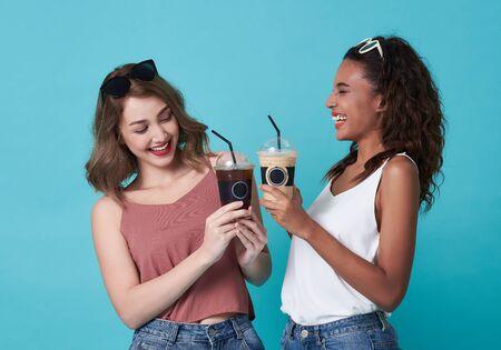 Coffee break, Happy women holding ice coffee on blue background.