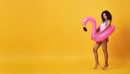 Happy smiling african woman dressed in swimwear holding flamingo rubber ring and enjoying their summer vacation getaway in yellow banner background with copy space. Banco de Imagens