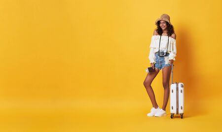 Happy smiling african woman dressed in summer clothes with luggage enjoying their summer vacation getaway in yellow banner background with copy space.