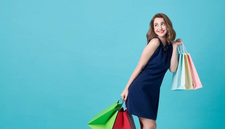 Happy beautiful young woman in blue dress and hand holding shopping bags and looking at on light blue banner background with copy space.