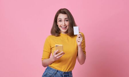 Excited happy young woman holding mobile phone and credit card isolated over pink background.