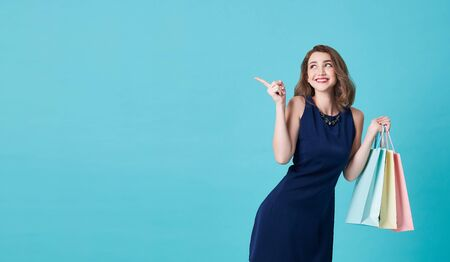 Happy beautiful young woman in blue dress with his hand holding shopping bags and finger pointing at on light blue banner background with copy space. Banco de Imagens