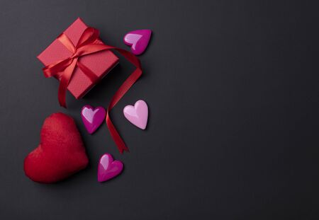 Valentines day background with red hearts and gift on black copy space background.