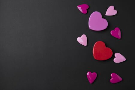Valentines day background with pink and red hearts on black copy space background.
