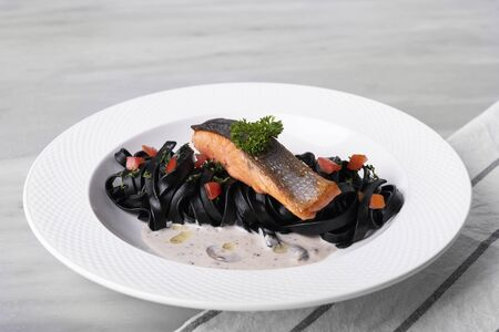 Salmon and Black pasta with tomatoes and parsley in white plate on table restaurant. 스톡 콘텐츠